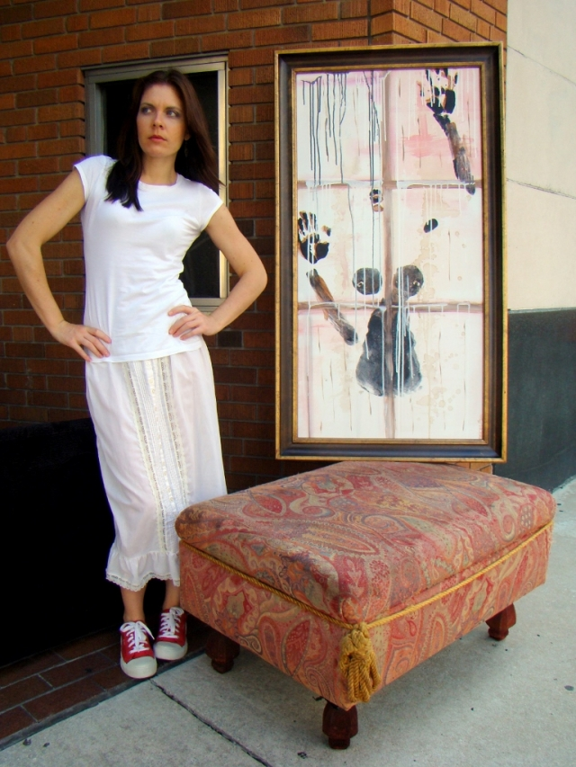 "Artist Rachael Harbert stands next to a sofa's ottoman sitting on a sidewalk with abstract expressionistic painting ""Against a Window"""