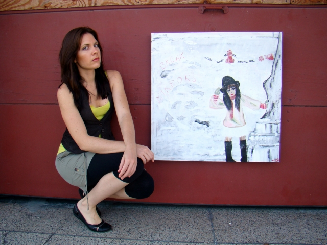"Artist Rachael Harbert crouches next to abstract painting ""Break Mirrors"" in front of a firehouse door"