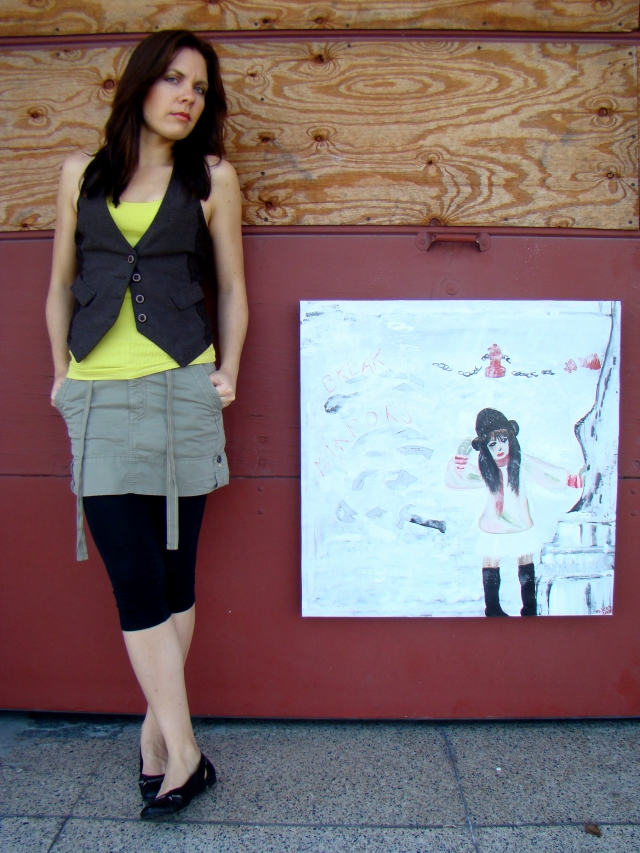 "Artist Rachael Harbert stands next to abstract painting ""Break Mirrors"" in front of a firehouse door"