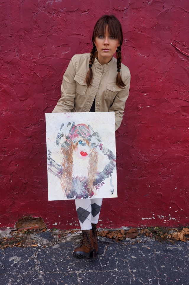 "Artist Rachael Harbert holds abstract painting ""Bundled"" in front of a red wall"