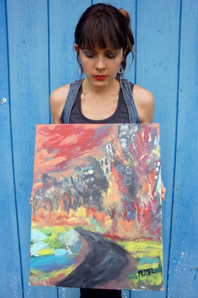 "Artist Rachael Harbert holding abstract expressionism painting ""Burning City"" in front of a blue wall"