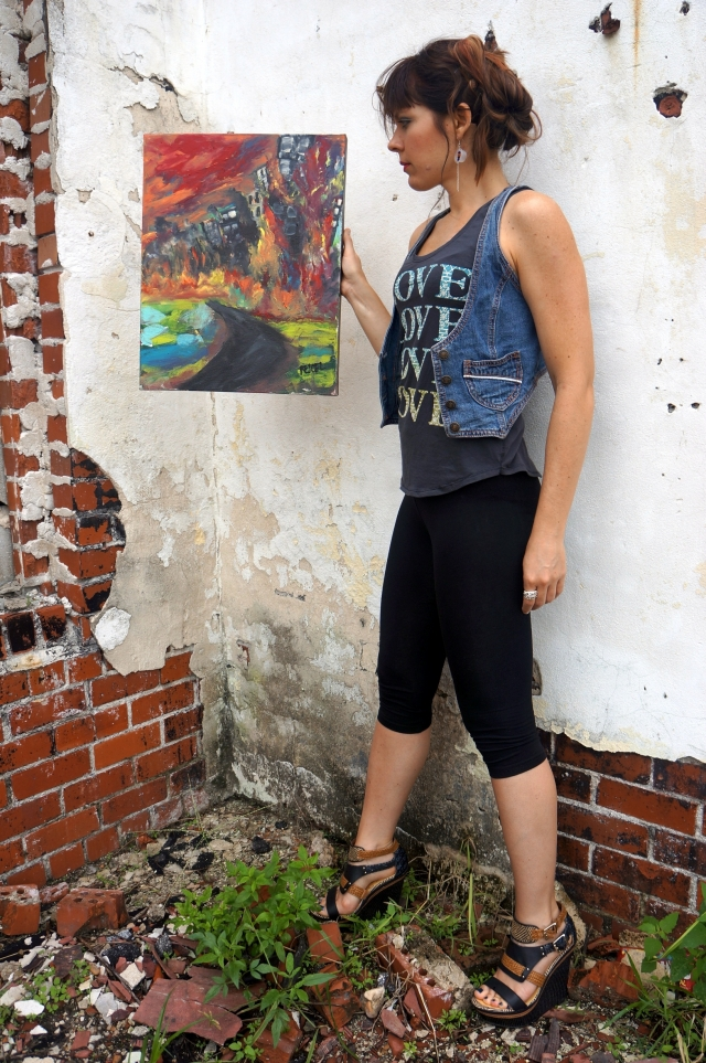 "Artist Rachael Harbert holding abstract expressionism painting ""Burning City"" next to a white cement and red brick wall"
