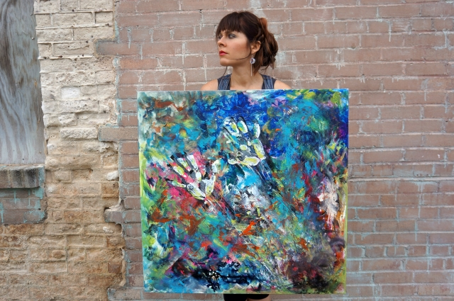 "Artist Rachael Harbert standing in front of a pink brick wall with abstract expressionism painting ""Electromagnetic"""