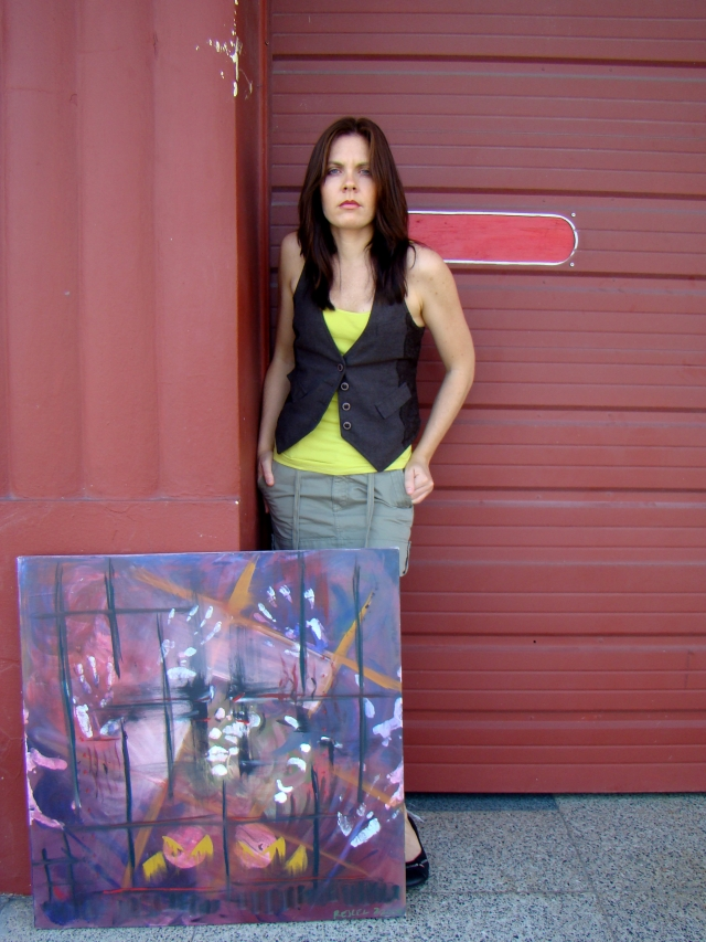 "Artist Rachael Harbert standing in front of firestation door with abstract expressionism painting ""Enclosed"""