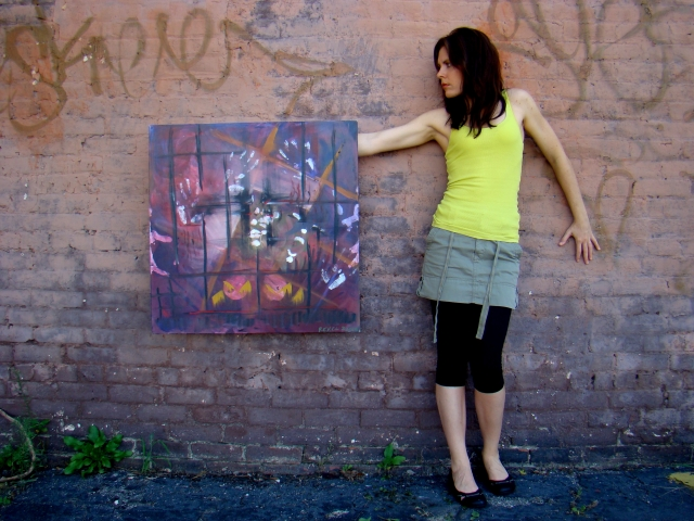 "Artist Rachael Harbert standing in front of brick and graffiti wall with abstract expressionism painting ""Enclosed"""