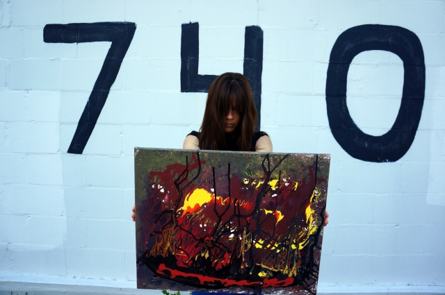 "Artist Rachael Harbert holding abstract expressionism painting ""The Fire Within"" in front of a wall with 740 painted on it"