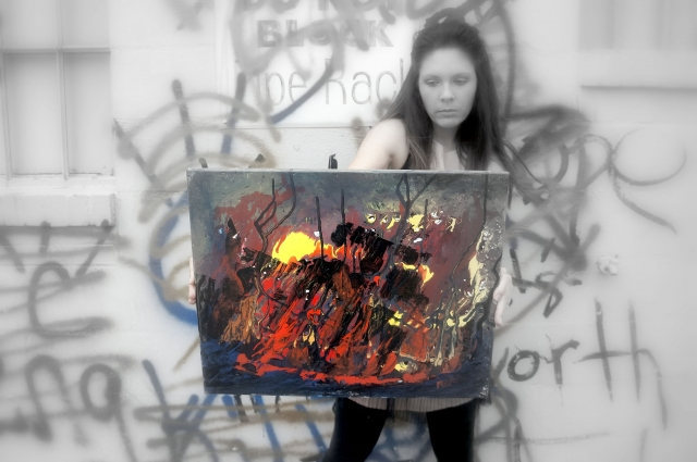 "Artist Rachael Harbert holding abstract expressionism painting ""The Fire Within"" in front of a graffiti wall - angle 1"