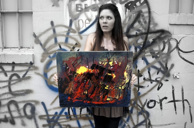 "Artist Rachael Harbert holding abstract expressionism painting ""The Fire Within"" in front of a graffiti wall - angle 2"