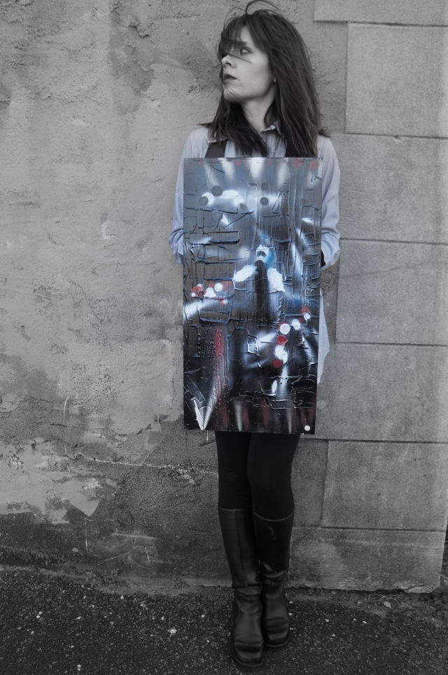 "Artist Rachael Harbert holding abstract expressionism painting ""Flashlights"" as she leans against a cement wall and the wind blows her hair into her face"