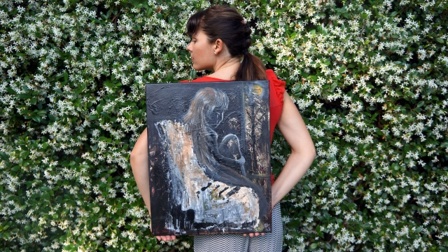 "Artist Rachael Harbert holds painting ""Forlorn"" in front of blooming jasmine vine"