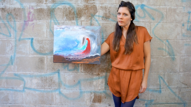 Artist Rachael Harbert holds painting Girl from the Sea in front of gray wall with blue graffiti