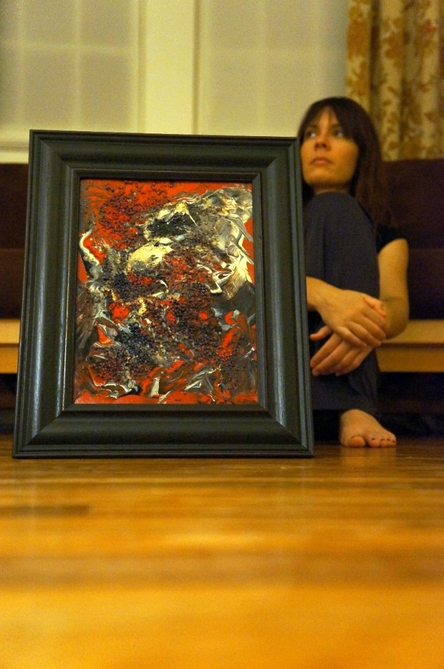"""Artist Rachael Harbert in background of abstract expressionism painting """"Gray Pebbles"""" in black wooden frame"""