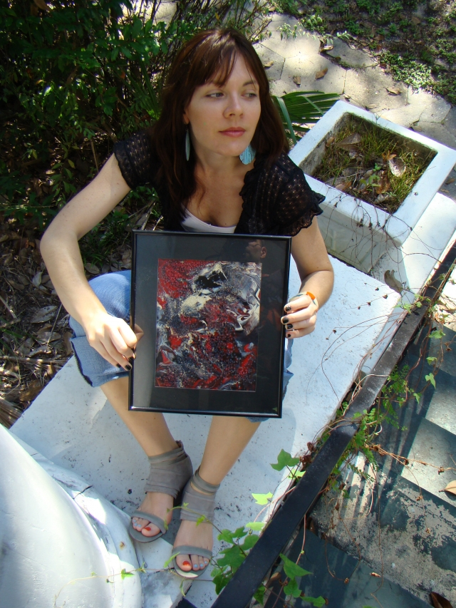 "Artist Rachael Harbert holding abstract expressionism painting ""Gray Pebbles"" as she sits on wide white step"
