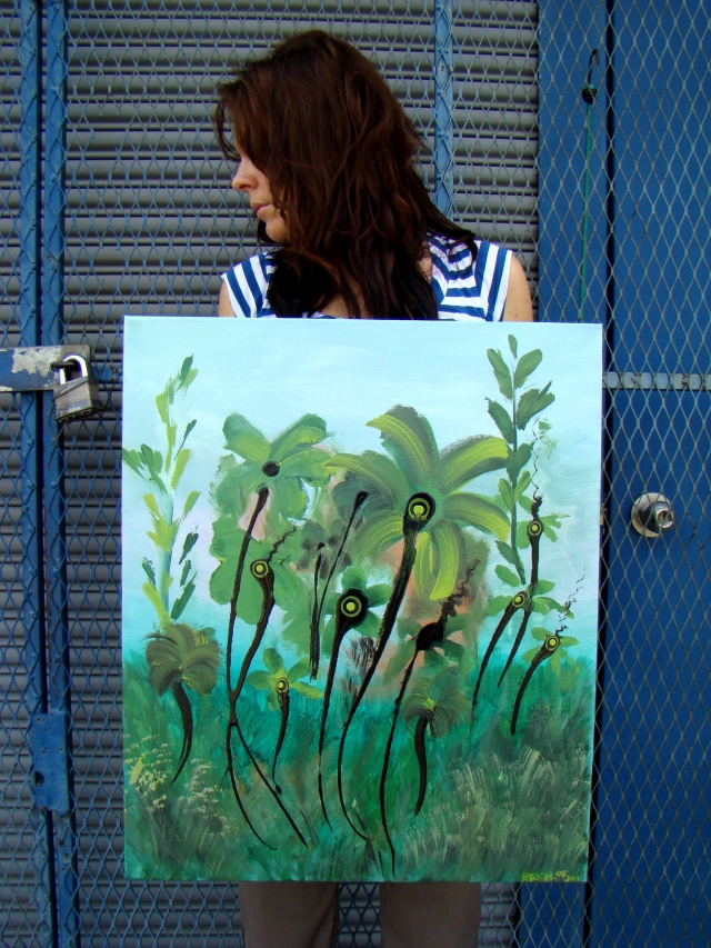 "Artist Rachael Harbert with first iteration of abstract expressionism painting ""Green Ballerinas"" while standing in front of a blue door"