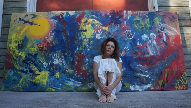 """Artist Rachael Harbert sitting in front of large abstract expressionism painting """"Human Explosion"""""""