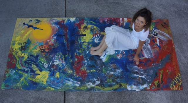 """Artist Rachael Harbert sitting on large abstract expressionism painting """"Human Explosion"""" and looking up"""