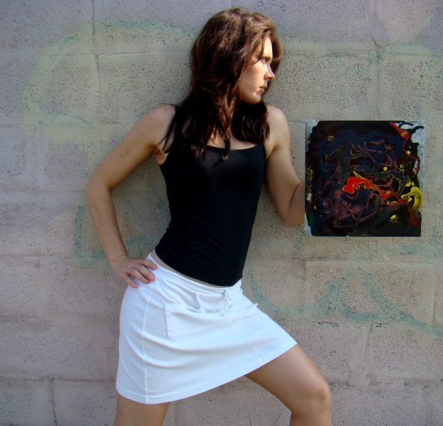 "Artist Rachael Harbert holds painting ""The Leaking"" in front of pastel graffiti wall"