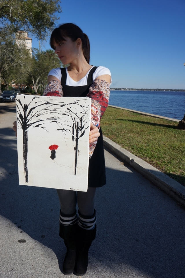 """Artist Rachael Harbert standing in the middle of the street holding abstract expressionistic painting """"A Lonely Walk"""""""