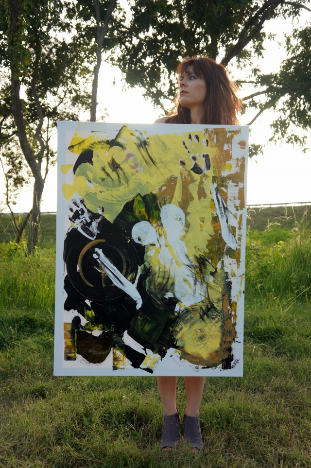 "Artist Rachael Harbert holding painting ""Luminescent"" as she stands on a grassy hill"