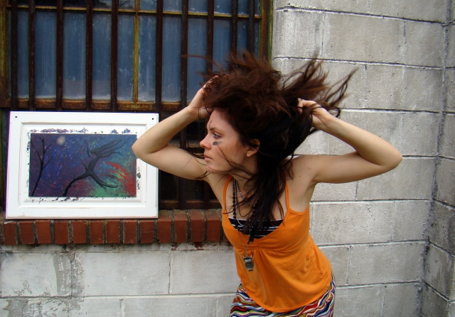 Artist Rachael Harbert looks at abstract expressionism painting Night Leaper as it sits on a window and her hair flies in the wind