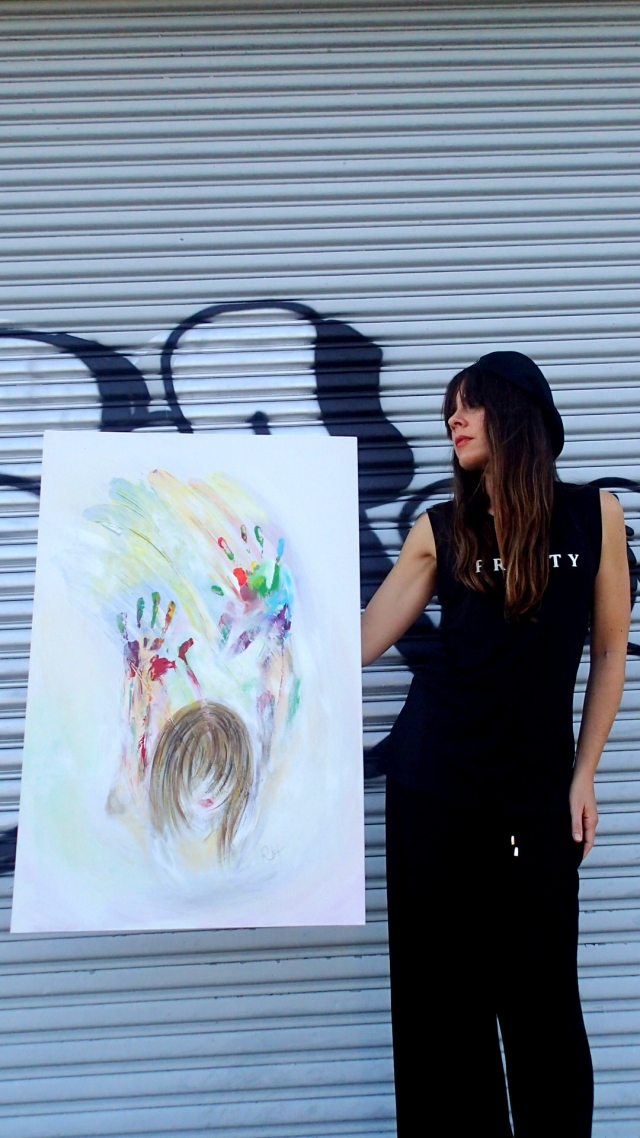Artist Rachael Harbert holds painting Opaline in front of metal door with black graffiti
