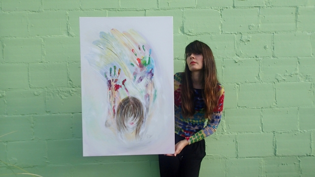Artist Rachael Harbert holds painting Opaline in front of green wall
