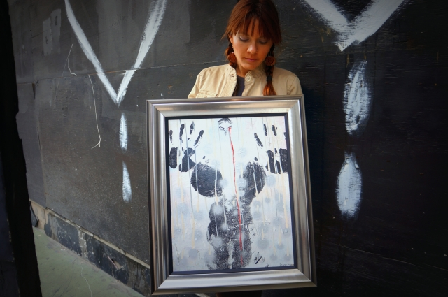 "Artist Rachael Harbert holding painting ""Pearls"" in front of a black wall with white dripping hearts"