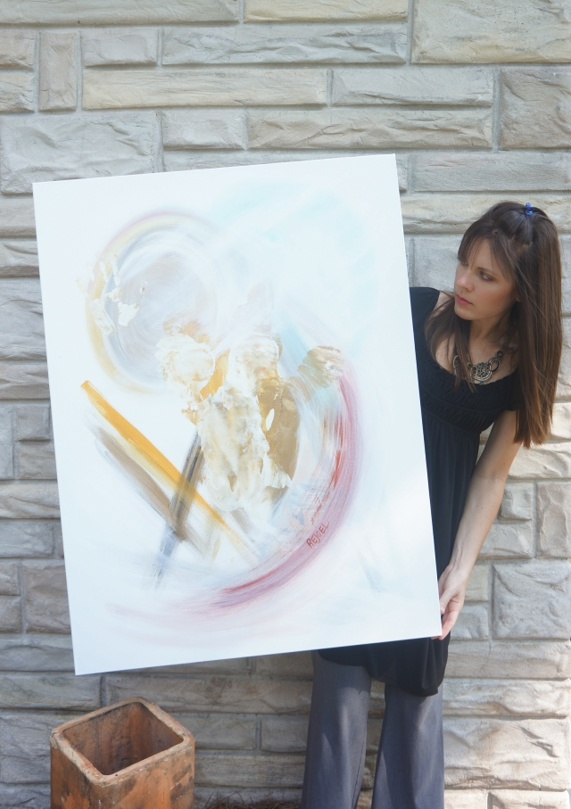 "Artist Rachael Harbert holds abstract expressionism painting ""Pendulum"" in front of a stone wall"
