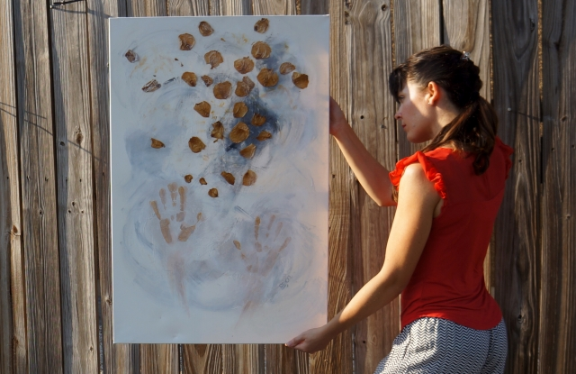 "Artist Rachael Harbert next to wooden fence facing the sun holding abstract expressionism painting ""Playing with Leaves"""