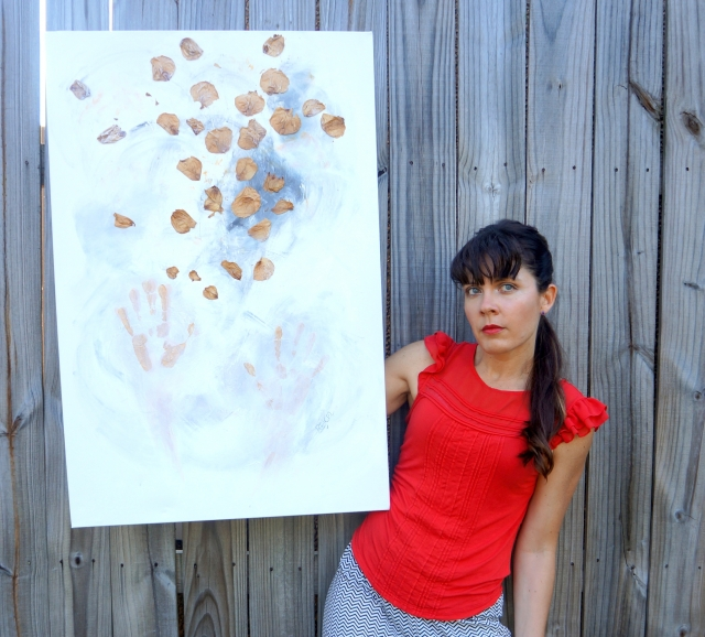 "Artist Rachael Harbert next to wooden fence holding abstract expressionism painting ""Playing with Leaves"""