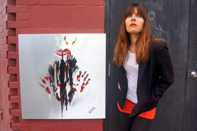 Artist Rachael Harbert standing next to abstract expressionism painting Quiet Now as it hangs on a black and red wall