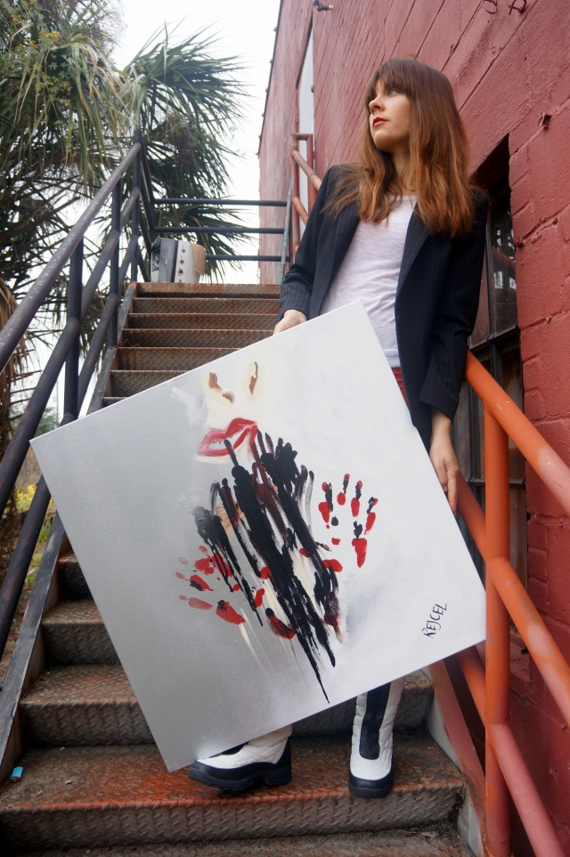 Artist Rachael Harbert propping up abstract expressionism painting Quiet Now as she stands on red metal stairs