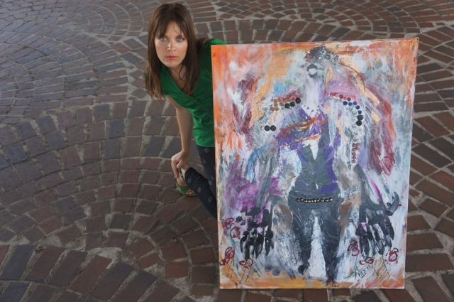 "Artist Rachael Harbert crouched down on a brick floor with abstract expressionism painting ""Animal"""