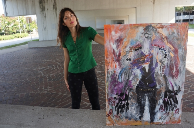 "Artist Rachael Harbert standing on a brick floor propping up abstract expressionism painting ""Animal"""