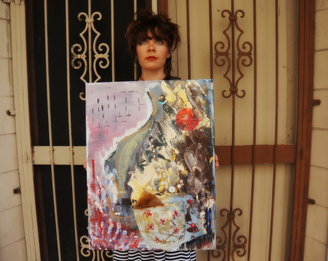 "Artist Rachael Harbert holds abstract painting ""Rachel"" in front of an iron door"