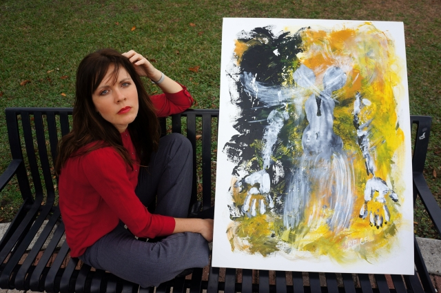 "Artist Rachael Harbert sits on a bench next to painting ""Regeneration"""