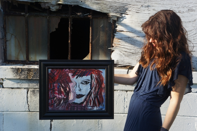 "Artist Rachael Harbert holds abstract expressionism painting ""Restless"" while looking at it"