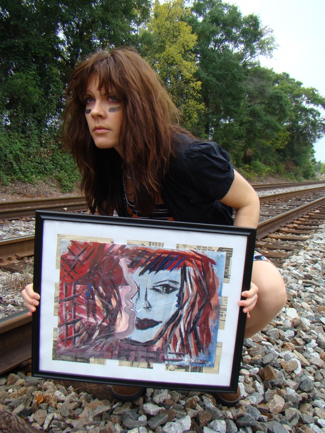 "Artist Rachael Harbert wearing war paint holds abstract expressionism painting ""Restless"" as she crouches next to train tracks"