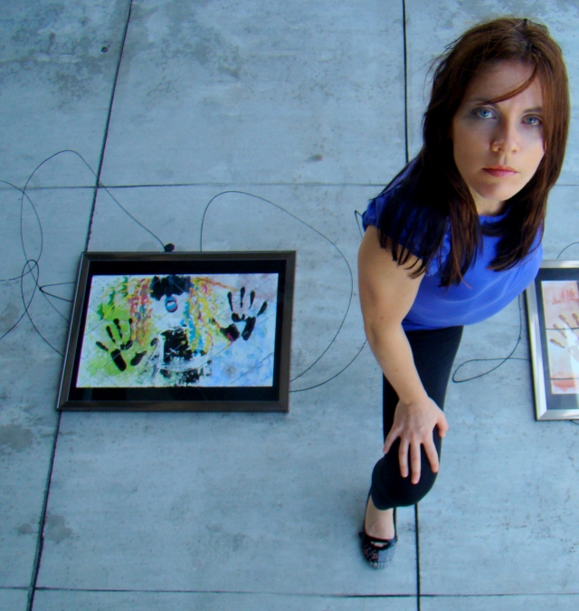 "Artist Rachael Harbert stands over abstract expressionism painting ""Retro Girl"" as it lies on a concrete sidewalk"