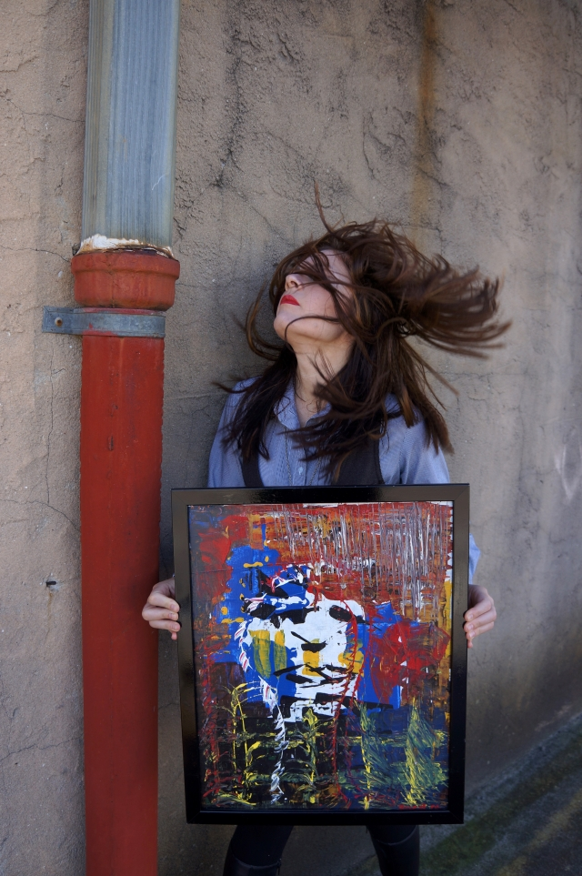 "Artist Rachael Harbert holds abstract expressionism painting ""Shards of Lust"" next to a concrete wall accented by a metal pipe"