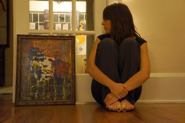 """Artist Rachael Harbert sits next to abstract expressionism painting """"Shards of Lust"""" in its ornate frame"""