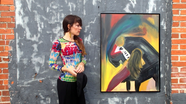 Artist Rachael Harbert holds painting The Soloist in front of a chalkboard and brick wall