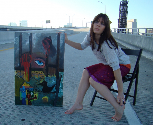 "Artist Rachael Harbert next to painting ""Strange Boxes"" in the middle of a bridge on-ramp"