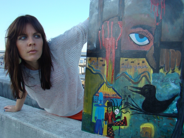 "Artist Rachael Harbert next to painting ""Strange Boxes"" on a bridge wall"