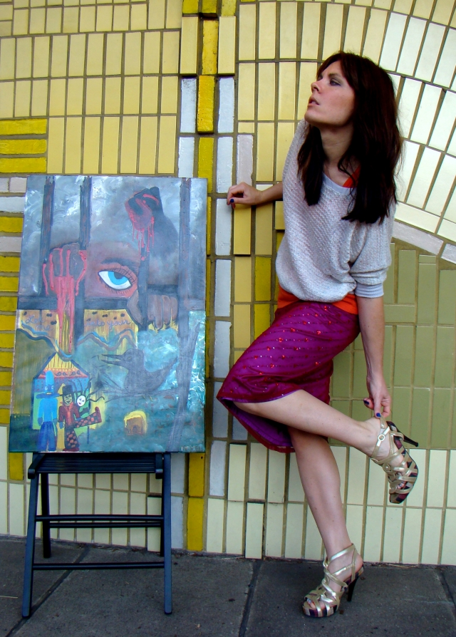 "Artist Rachael Harbert next to painting ""Strange Boxes"" in front of yellow tiled wall"