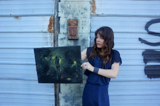 "Artist Rachael Harbert holds abstract expressionism painting ""Stranger in the Alley"" in front of wall with ""Sold"" written on it - 2"