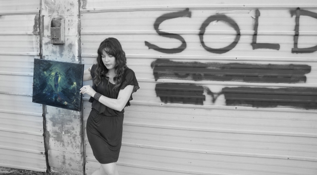 "Artist Rachael Harbert holds abstract expressionism painting ""Stranger in the Alley"" in front of wall with ""Sold"" written on it - 1"