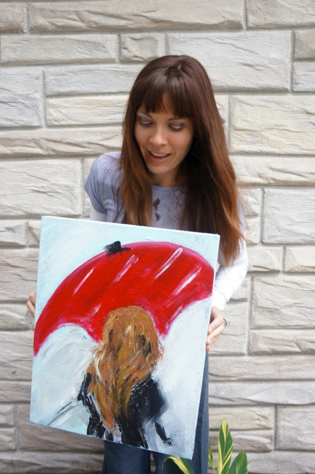 "Artist Rachael Harbert standing in front of a stone wall holding abstract expressionistic painting ""Through the Rain"""