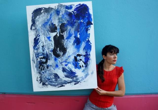 "Artist Rachael Harbert next to a pink and blue wall holding abstract expressionism painting ""Under Water"""