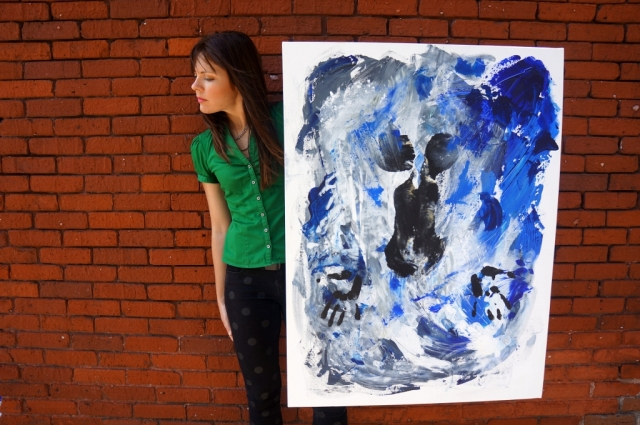 """Artist Rachael Harbert next to a brick wall holding abstract expressionism painting """"Under Water"""""""